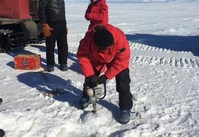 Hanna drilling into a sea ice crack to measure depth