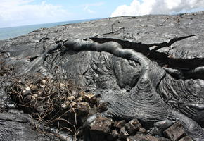 Recent lava overtaking old beach rock wall